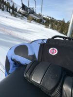 Arctica mittens on lift chair next to rear wearing Arctica GS Speed Suit and Arctica Black Kat Shorts
