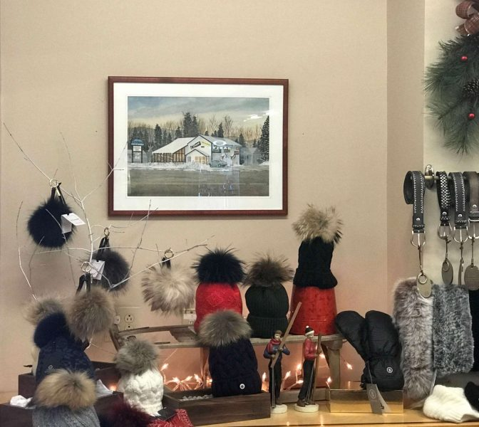 A painting of Rodgers Ski & Sport's original location on display with beautiful ski accessories for women.